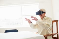 Senior man using an oculus rift Kuvituskuvat