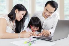 Young parents teach their child at home - stock photo