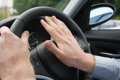 A man pressing a car horn - stock photo
