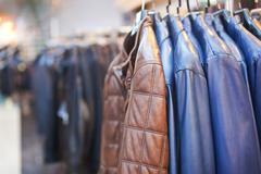 Collection of leather jackets on hangers in the shop Stock Photos