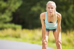 Slim young woman catching her breath after a long run Stock Photos
