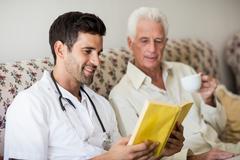 Nurse and senior man reading a book Stock Photos