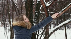 Woman shakes off the snow from the tree Stock Footage