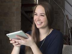 Young woman in good mood looks in tablet Stock Photos