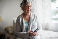 Senior woman sending a message with her smartphone Stock Photos