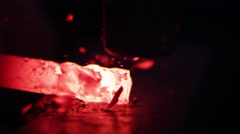 Red hot metal being hammered on anvil up close Stock Footage