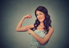 Fit young healthy model woman flexing muscles showing her strength Stock Photos
