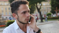 Young man have a serious talk on cellphone in the city center. Male in his 20s - stock footage