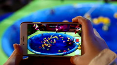 Recording children playing fishing game on iphone - stock footage
