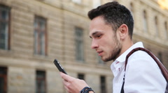 Attractive guy watching on a phone screen and smiling. Positive male in his 20s - stock footage