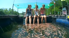 Three girls at the spa procedures, Mozambique tilapia (Oreochromis mossambicus) Stock Footage