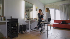 The friendly stylist working with his regular customer in a beauty salon - stock footage