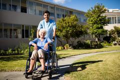 Nurse pushing the senior womans wheelchair Stock Photos