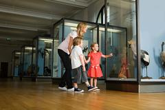 Mother and children looking at a museum exhibit Stock Photos