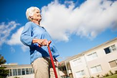 A senior woman walking with her walking stick Stock Photos
