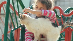 Girl teen stroking a cat on outdoors playground Stock Footage