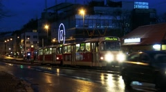 Tram and cars go on road at night in town Stock Footage