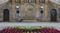 Flowers in garden with stone wall fountain Stock Footage
