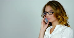 Young attractive woman talks on telephone and moves her gaze, reflections on her - stock footage