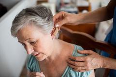 Nurse putting hearing aid to a senior woman Stock Photos