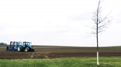 Tractor driver stand at big blue tractor on ploughed up field Stock Footage