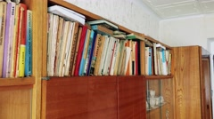 Books put in row in bookshelf in old cupboard  Stock Footage