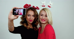 Two young cheerful female models with christmas accessories in their heads make Stock Footage