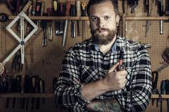 Environmental portrait of a man smoking pipe in wood workshop Stock Photos