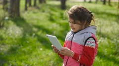 Girl teen with a tablet in spring on background of green grass in the forest Stock Footage
