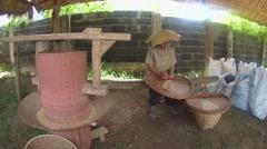 An elderly Thai woman cleans grain rice, Loei province, Thailand Stock Footage