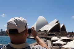 A tourist photographing sydney opera house - stock photo
