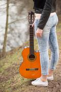 Woman legs in blue jeans, orange guitar on white shoes Stock Photos