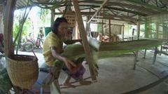 An elderly Tai Dam woman working on old bamboo loom, Loei province, Thailand Stock Footage