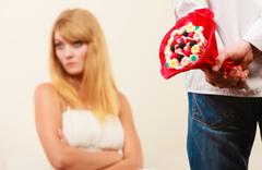 Man with candy bunch flowers and unhappy woman. - stock photo