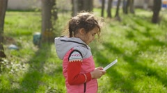 Girl teen with tablet in spring on background of green grass in forest plays in Stock Footage