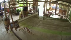 An elderly Tai Dam woman working on old bamboo loom, Loei province, Thailand Stock Footage