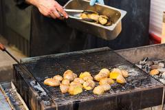 Tasty potatoes prepared on hot BBQ charcoal. - stock photo