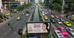 Busy Road in Bangkok with camera tilt up skin whitening advert on billboard - stock footage