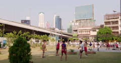 Young asian men playing football in a park in Bangkok Stock Footage