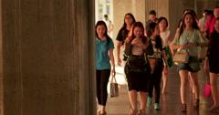 Fashionable dressed asian teen girls walking looking at mobile phones / talking Stock Footage