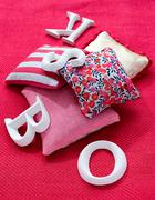 Cushions and letters on a carpet - stock photo