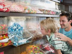 A father and son choosing sweets - stock photo