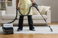A man vacuum cleaning Stock Photos