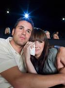 A man comforting a woman watching a sad movie - stock photo