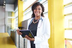 Portrait of a female doctor holding her patient chart on digital tablet in - stock photo