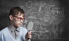 Curious school boy with magnifier Stock Photos