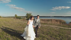 The groom and the bride run. Aerial shot. The Evening Lake Stock Footage