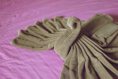 Close up brown towel plait as swan on purple bed Stock Photos