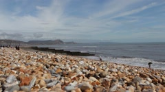 Tourists on the pebble beach at Lyme Regis Stock Footage