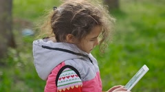 Girl teen with tablet in spring on background of green grass in the forest plays Stock Footage